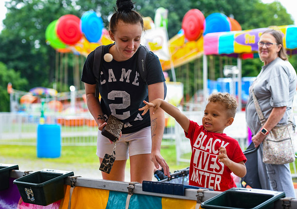 Qhalid Morrison, 3, throws a ping pong ball in hopes of winning a goldfish as his mom Karina, left, looks on during the opening day of the Cass County Fair in Logansport on Sunday, July 11, 2021.