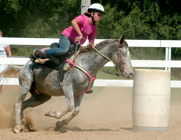 In this photo taken Monday, July 7, 2014, Bailey Schmid maneuvers her horse around one of three obstacles during barrel racing competition at the Cass Co. 4-H Fair in Logansport IN. (AP Photo/Logansport Pharos-Tribune, Steve Summers)