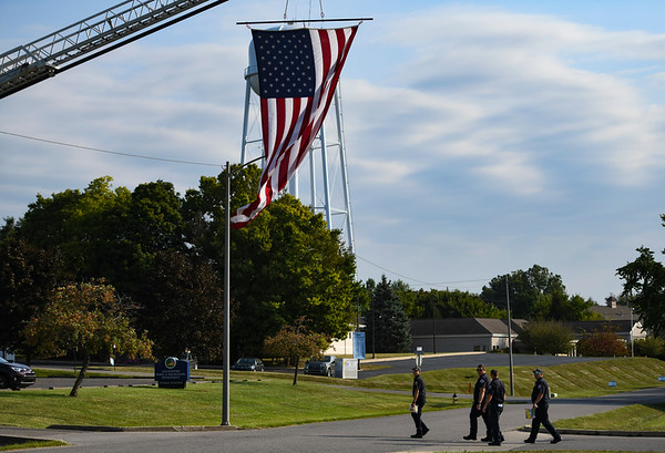 First responders walk under a large flag during a 9/11 remembrance 5K run and dog walk event hosted by the Logansport Police Department at Huston Park in Logansport on Saturday, Sept. 11, 2021.
