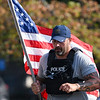 Police Chief Travis Yike runs with an American flag during a 9/11 remembrance 5K run and dog walk event hosted by the Logansport Police Department at Huston Park in Logansport on Saturday, Sept. 11, 2021.