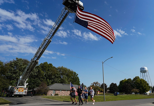 A group runs under a large flag during a 9/11 remembrance 5K run and dog walk event hosted by the Logansport Police Department at Huston Park in Logansport on Saturday, Sept. 11, 2021.