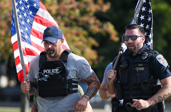 Police Chief Travis Yike runs alongside patrolman Branson Eber during a 9/11 remembrance 5K run and dog walk event hosted by the Logansport Police Department at Huston Park in Logansport on Saturday, Sept. 11, 2021.