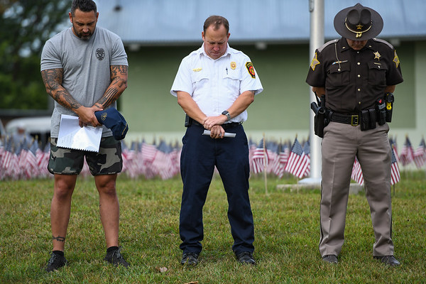 From left: Police Chief Travis Yike, fire Chief Rick Bair and Sheriff Ed Schroeder bow their heads during a 9/11 remembrance 5K run and dog walk event hosted by the Logansport Police Department at Huston Park in Logansport on Saturday, Sept. 11, 2021.