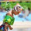 Jadyn Diaz smiles as water falls on his cap at the Muehlhausen Park splash pad in Logansport on Wednesday, July 28, 2021.
