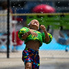 Jadyn Diaz smiles as water drops fall on him at the Muehlhausen Park splash pad in Logansport on Wednesday, July 28, 2021.
