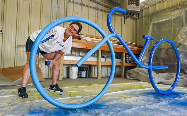 Vickie Lebo applies a coat of paint to a bike rack during a Live United Day project at Steinberger Construction in Logansport on Friday, Sept. 10, 2021.