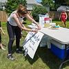 Alyssa Irvin, center, tapes the lemonade stand sign tot he table as Oliver Stillabower, 7, looks on Thursday, June 10, 2021 in Logansport.