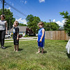 Alyssa Irvin, left, helps Oliver Stillabower, center, and his friend Noah attracts cars to the lemonade stand by waving on Thursday, June 10, 2021 in Logansport.