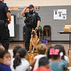 Officer Cody Scott and his K-9 Snupy stand in the gymnasium at Columbia Elementary School during a presentation to students by officers from the Logansport Police Department on Tuesday, Sept. 21, 2021.
