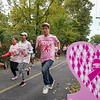 Runner race past pink hearts during the River Bluff Fun Run and Walk at the River Bluff Trail in Logansport on Saturday, Oct. 2, 2021.