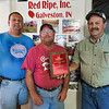 """From left: Kory, Kurt and Kevin Wilson pose with their """"Master Grower"""" award from Red Gold Tomatoes in Galveston on Tuesday, July 6, 2021."""