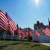 Thirteen flags stand in the yard of a home near the intersection of 21st and Jefferson streets on Tuesday, Aug. 31, 2021, to honor the servicemen killed last week.
