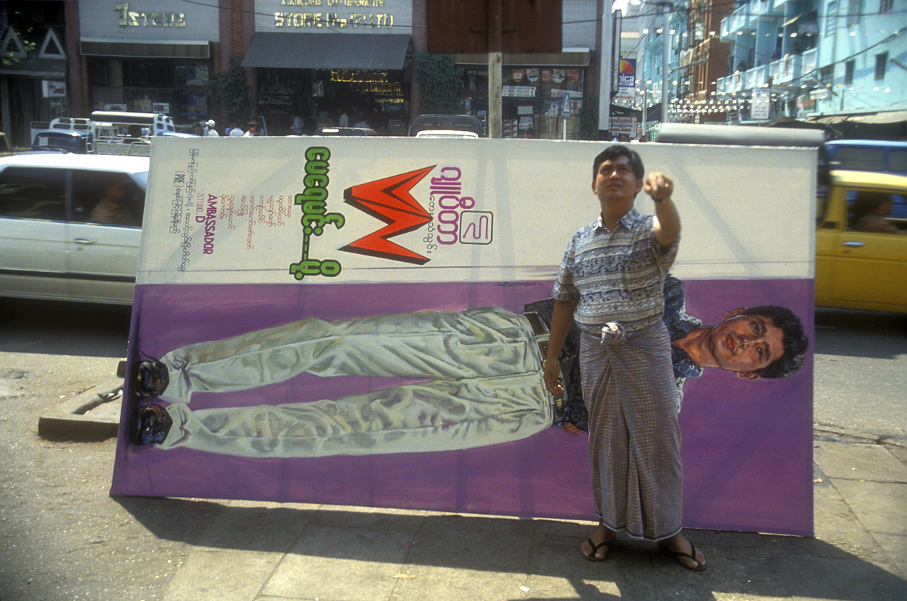"""Ad man in his longyi - as Kyaw explained, they're """"long - yee's"""" here, """"lon - gee's"""" in India. Rangoon."""
