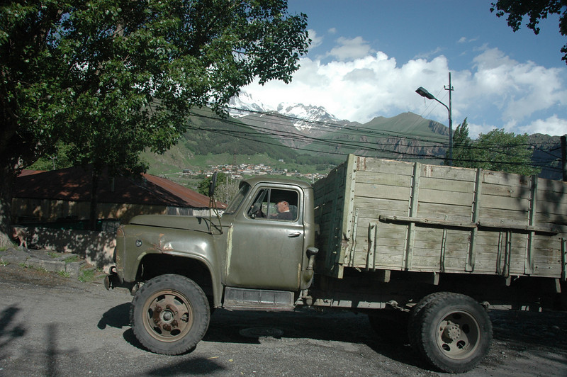 """A dump truck-sized Kamaz lumbered by, an unlikely family vehicle that deposited a scarf-clad old woman with a basket down at the bottom of the hill."" The family car, Kazbek, Republic of Georgia."