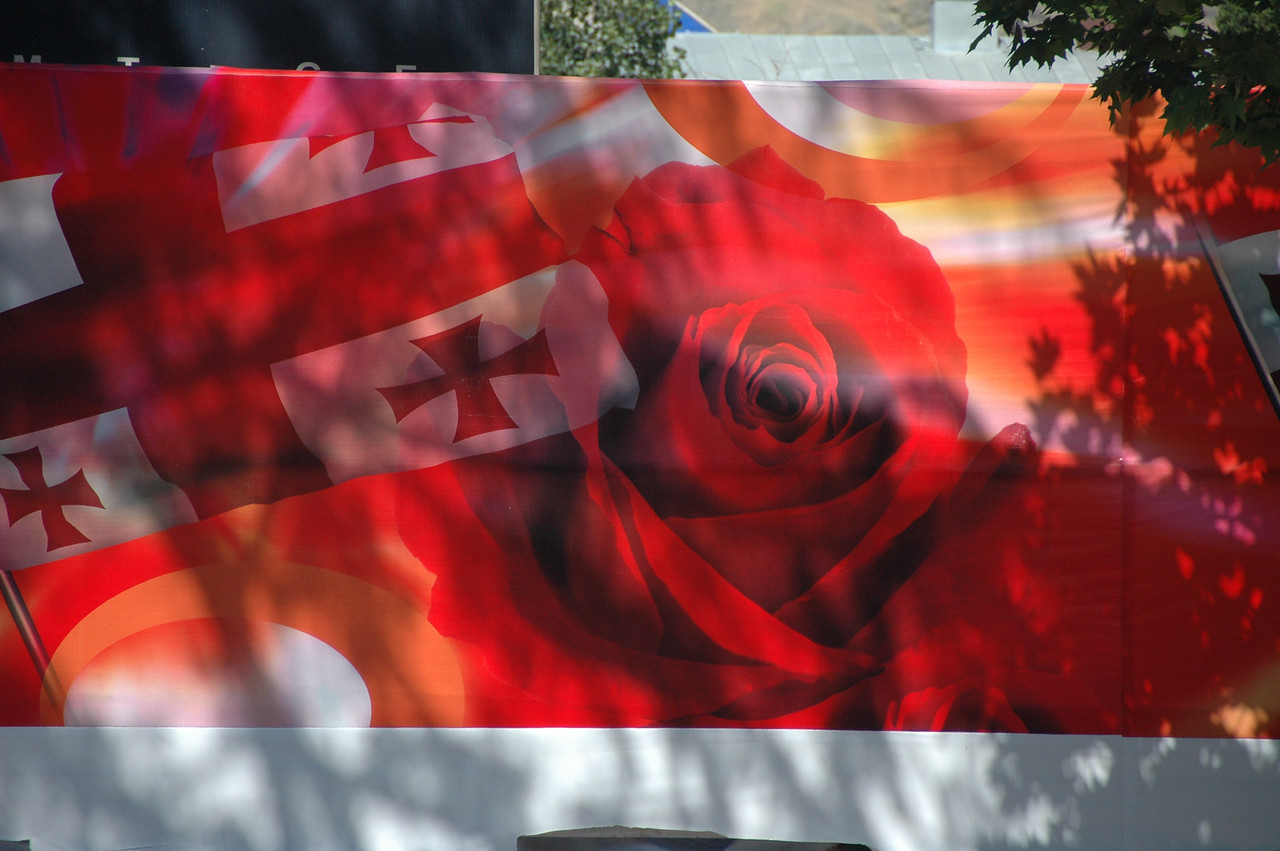 """Georgia's """"color revolution"""" was called the """"rose revolution,"""" and took place in November 2003. This billboard celebrates the revolution, with rose and national flag, in downtown Tbilisi."""