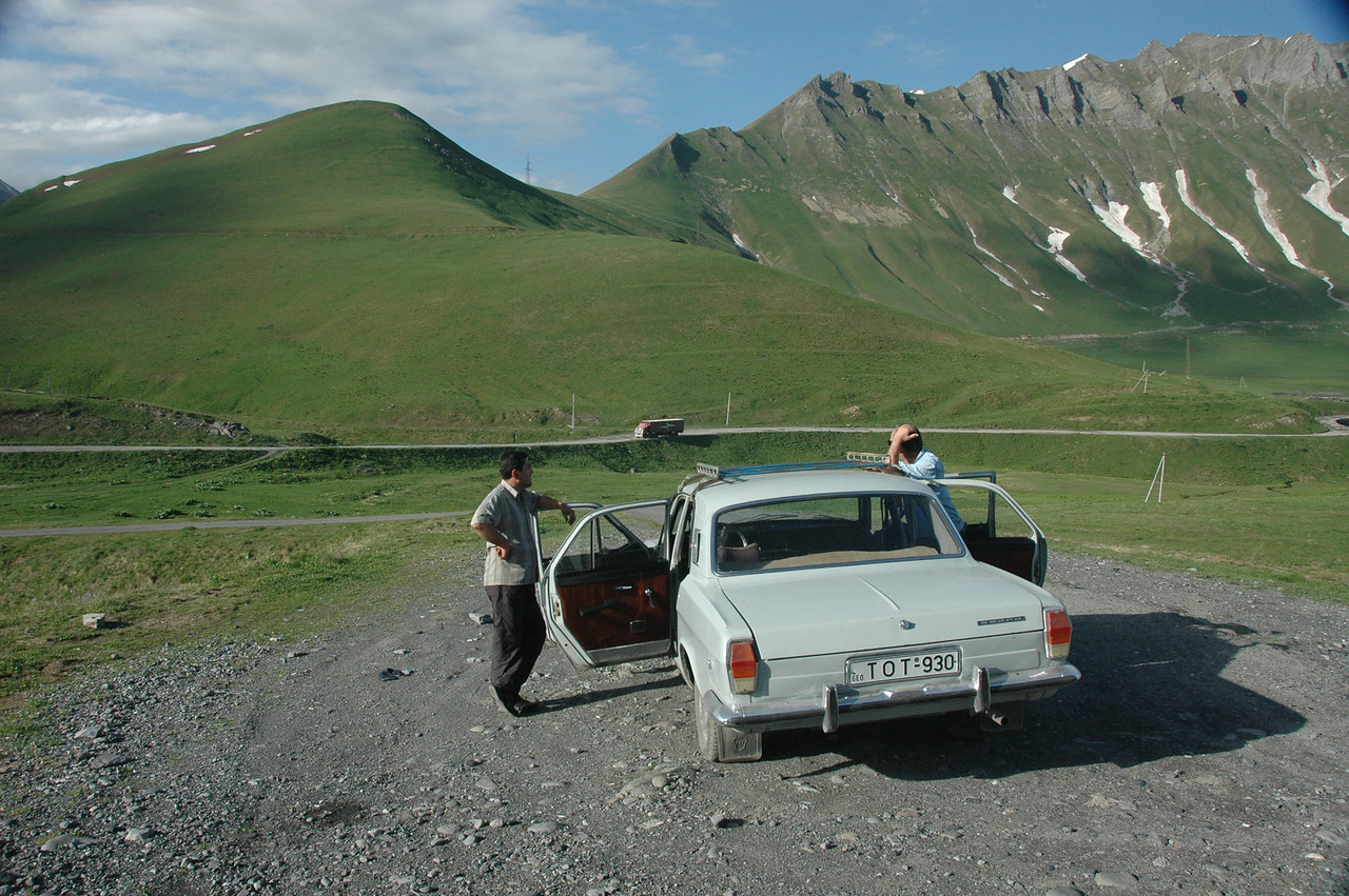We stopped to peer over a precipice – the verge of a steep defile, at2395 meters, in intermittent ice fields, with streams and more lavender and yellow flowers. This is looking back the other way, at Zviadi,left, and Zaza.