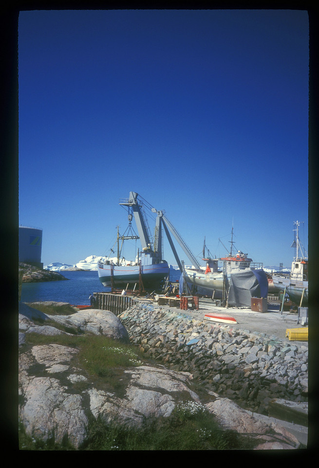 Like most outposts, Ilullisat puts on a working face, presenting things like the storage tank at left to the visitor arriving by sea. Here's the harbor at Ilullisat.