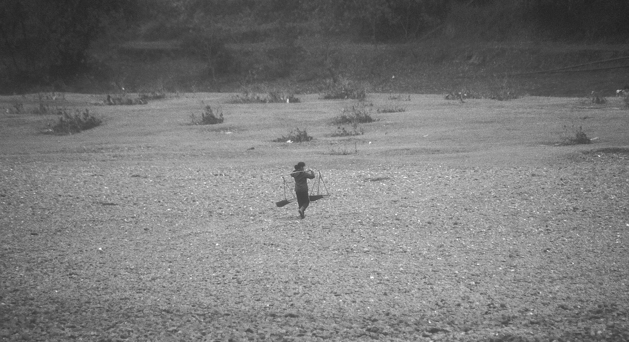 This lady walks on the Li floodplain, and this shot was taken from the ship. Can't tell what she's carrying.