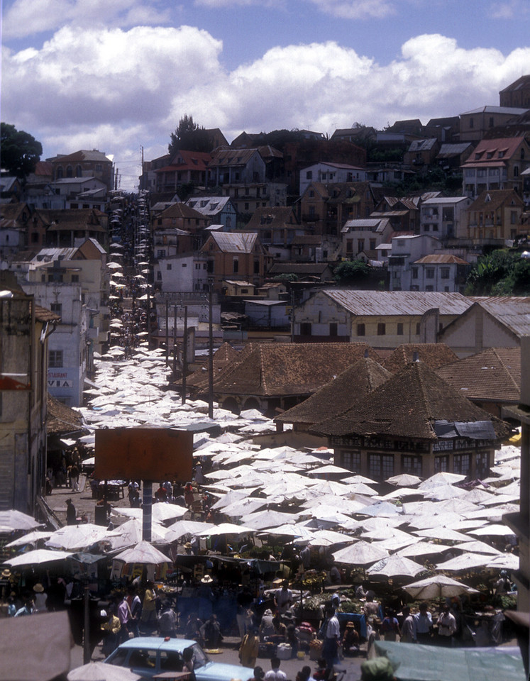 Zoma means Friday and it's also the name for the positively teeming Friday market in Madagascar's capital city, Antananarivo. White umbrellas wash out ahead in every direction, swallowing up the main square, flowing into busy little eddies beside stairways, up the hills as far as the eyes can see.