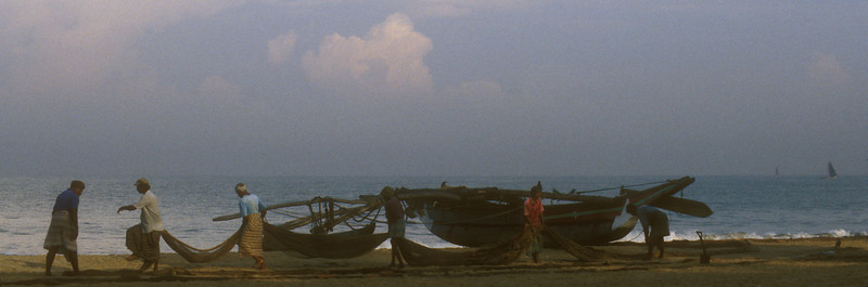 Some of the fishing fleet was already back on Negombo Beach shortly past dawn. Here they're stepping over nets, untangling and setting them right for the afternoon.