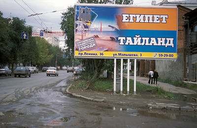 Muddy E-kat, east of the Urals. It would appear that getting away is on the minds of the locals. This billboard siggests taking a trip to Egypt or Thailand.