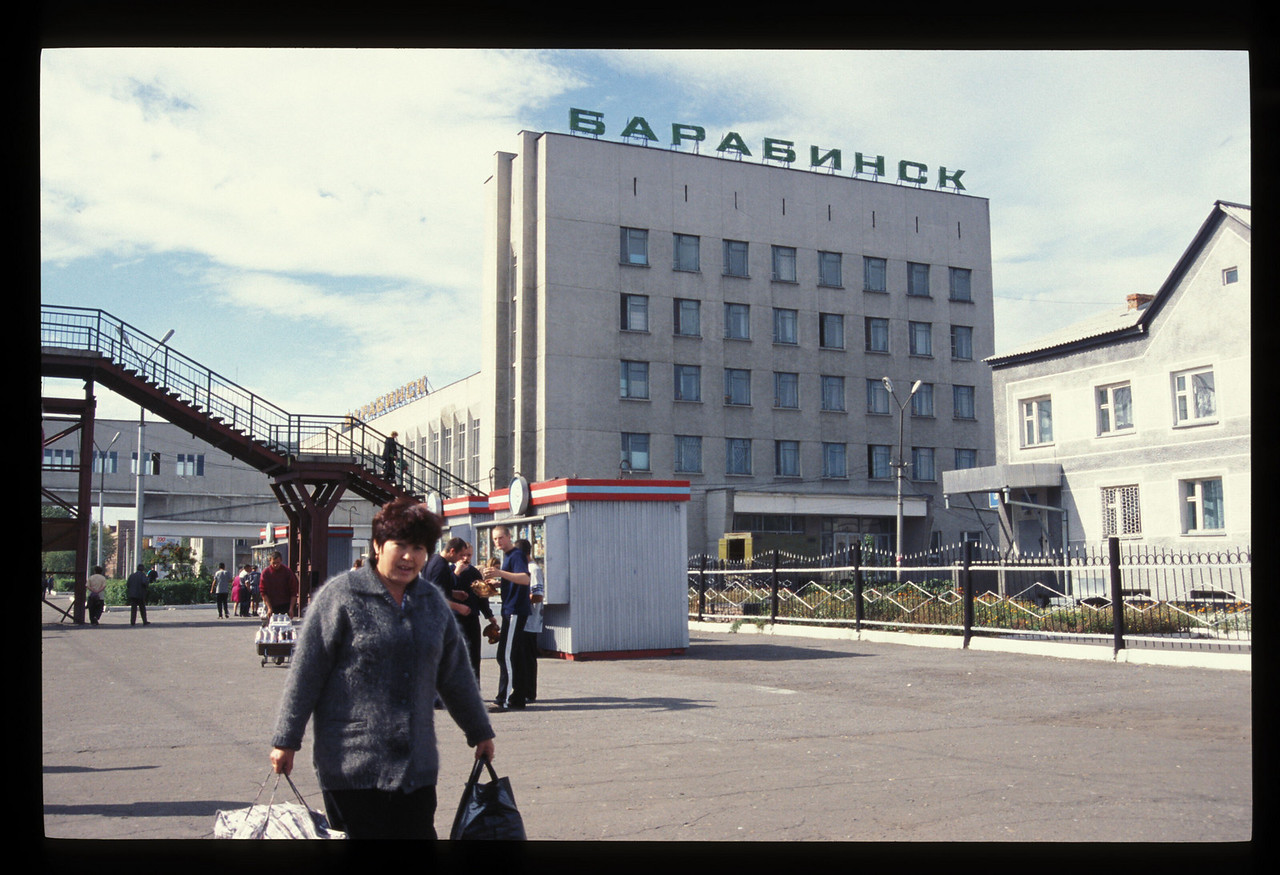 """""""Must've been 68 or 70 degrees, perfect air, as we all clambered out to stretch. They sold tons of some particular flayed and dried fish. The good people of Barabinsk still looked thoroughly European, not a bit Asian.""""<br /> <br /> Barabinsk rail station, Novosibirsk Oblast, Russia."""