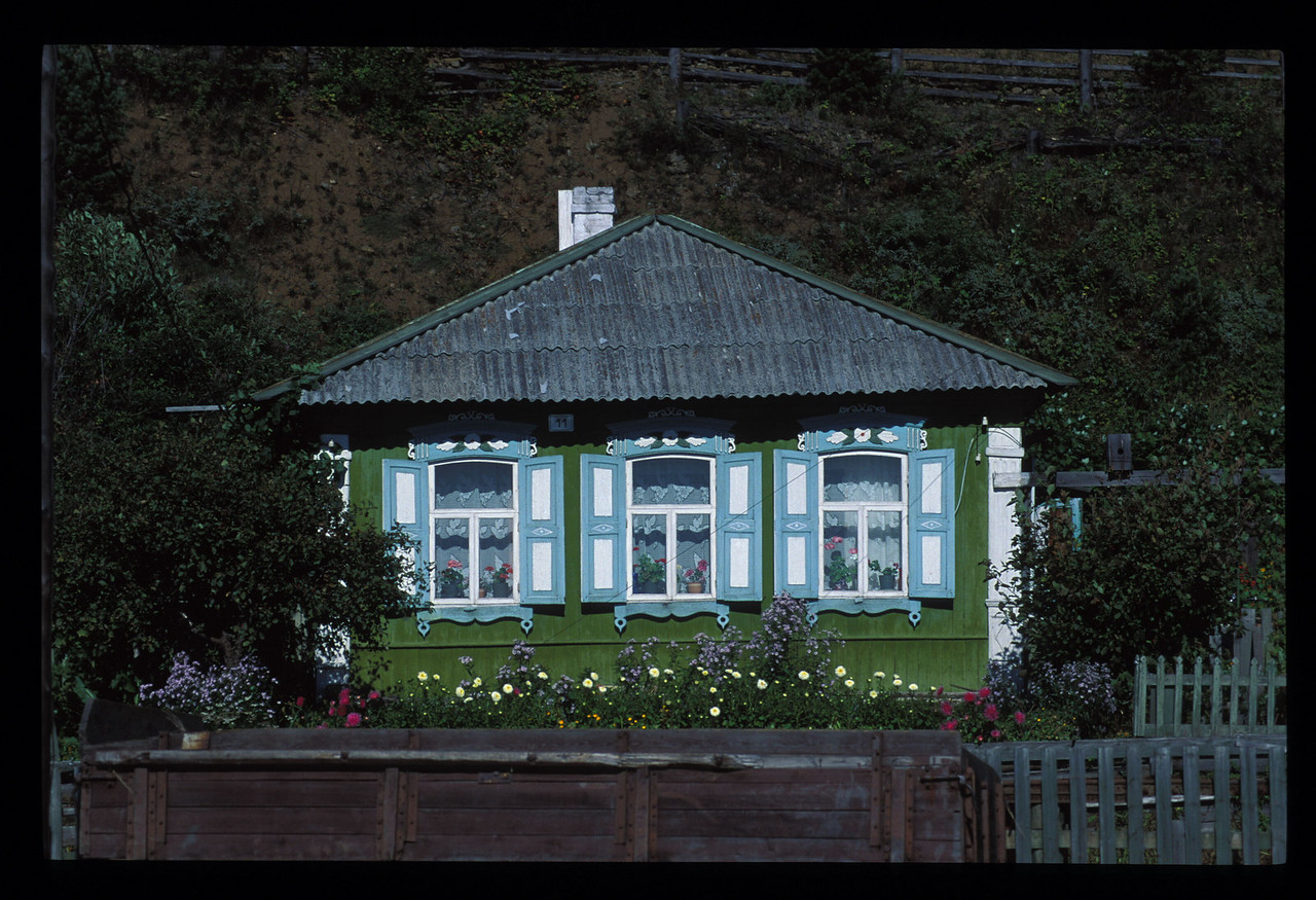 """""""East of Barabinsk a particular aquamarine colored paint took hold of all the buildings."""" <br /> <br /> Typical house between Omsk and Novosibirsk, with shutters of that aquamarine color."""