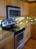 granite countertops, glass tile backsplash and Hertco custom cabinets