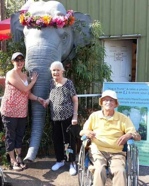 Title: The Elephants are Here<br /> Caption: Dawn, Elnora and Richard pose with an elephant (not a real one) at the Nevada County Fair. 'Have Trunk Will Travel' brought two of their real elephants to give rides.  <br /> Photographer: Helen Vanderhoof, Golden Empire Nursing & Rehab Center, Grass Valley.