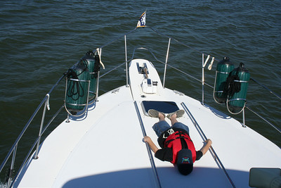 """Relaxing on the bow while cruising the Chesapeake Bay.  Life jacket on and hands on rail.\"""