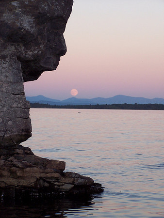 Full moon rising over the Green Mountains of Vermont on Lake Champlain