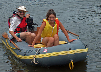 Grandfather and granddaughter wear their PFDs even while dinghy riding in a quiet creek.