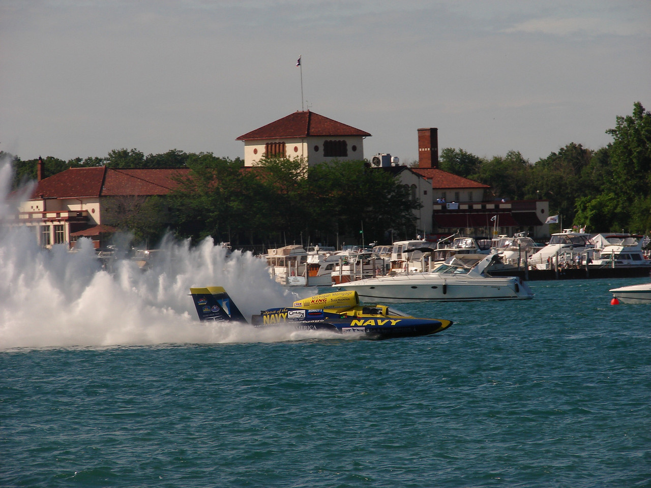 The foreground boat, sponsored by the Navy, was probably traveling 150-155 mph when the photo was taken. In the middle ground is Detroit Power Squadron's P/C Mitch Gawrysiak's 44 Formula, a course judging and rescue boat. There were at least six or seven other DPS members. There were at least 5 other Detroit members boat working the course also. In the back ground, the Detroit Yacht Club has been DPS's home since 1936.