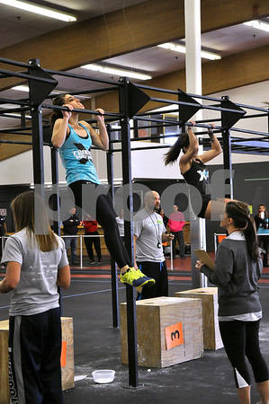 -Messenger photo by Joe Sutter<br /> <br /> Cali Olson, left, of Webster City, and Colleen Halligan, Fort Dodge, complete as many chin-ups as possible in a minute during the second set of workouts in the Iowa Gladiator Games Saturday afternoon at the REC Coliseum.
