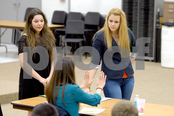 -Messenger photo by Hans Madsen<br /> <br /> Jamila Shing-Hon, 17, left, and Madeline Ascherl, 18, get feedback from speech judge Lindsay Mickelson, of Des Moines, during the District Large Group Speech Contest at Fort Dodge Senior High School. The two Fort Dodge students performed two poems.