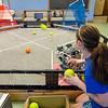 Charlotte Weldon, part of the Robo Mayhem robotics team, feeds foam balls into a robot that shoots them off into a net on Wednesday evening. SENTINEL & ENTERPRISE / Ashley Green