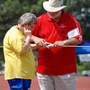A volunteer guides a visually impaired woman to the rope she'll hold while competing in a walking race.