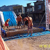 The  race workers are preparing the mud pit at the end of the race.