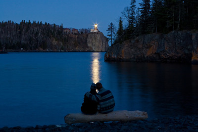A young couple sit on on the cool Lake Superior beach watching the beacon at Split Rock Lighthouse.Photographers Name : Dennis O\'HaraPhotographers City and State : Duluth MNTo vote in favor for this photo, simply add a comment below. You can also share this photo on Facebook and Twitter using the buttons above.