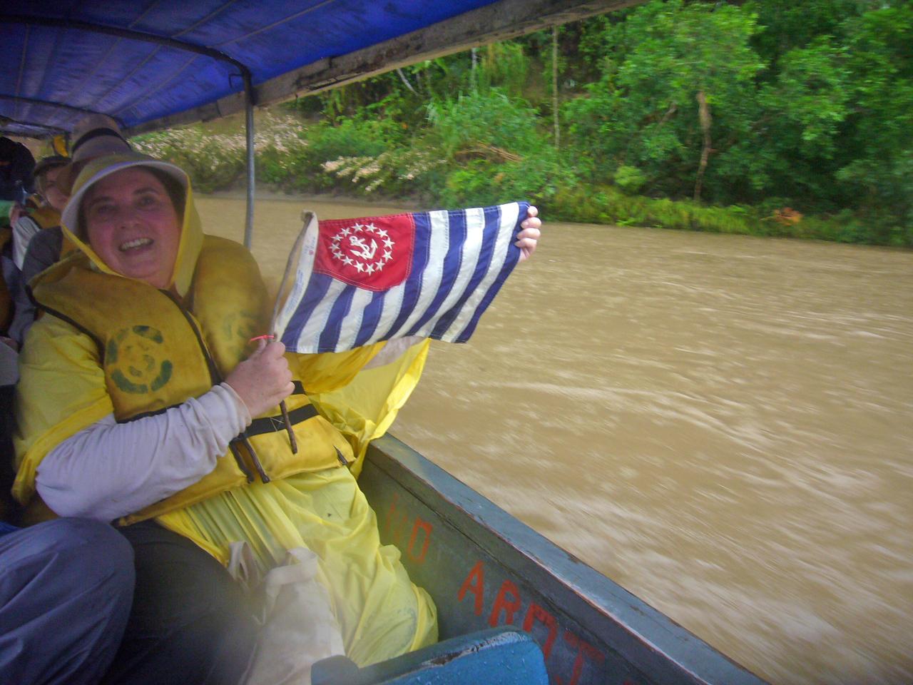 P/DLt Marilynn Bezdek AP proudly displays the USPS Ensign during a rainstorm on the Napo River, Ecuador - William Bezdek