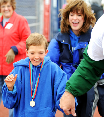 Charles R. Wood, 13, of Carthage, shows his excitement after being awarded a gold medal by volunteer David Thompson, field coordinator for low mobility, during the Special Olympics Friday morning, April 20, 2012, at MSSU's Fred G. Hughes Field. Wood's mother Gayle Wood smiles from behind him. Globe/T. Rob Brown