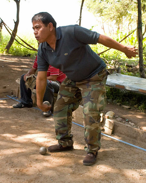 Lao Man Competing In A Game of Petanque Along the Banks of the Mekong River