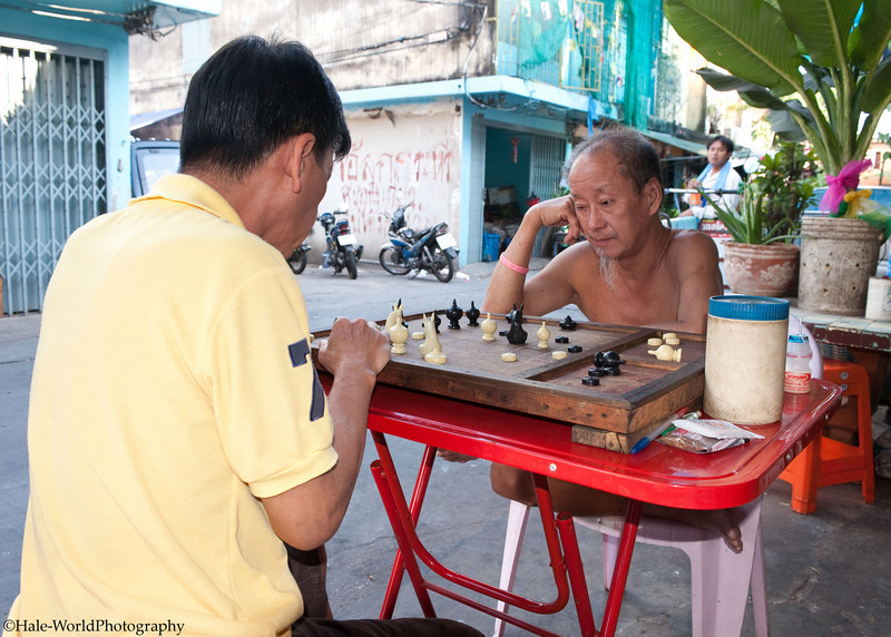 Contemplating the next move during a game of chess between Bangkok neighbors