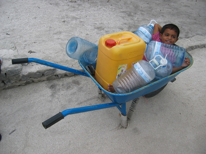 Little boy with water bottles. Credit: Red Cross
