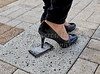 Spiked Heel of a Womans Shoe stepping on a Cell Phone