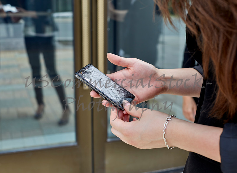 Woman holding a Broken Cell Phone