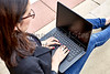Young Woman typing on Keyboard of Laptop