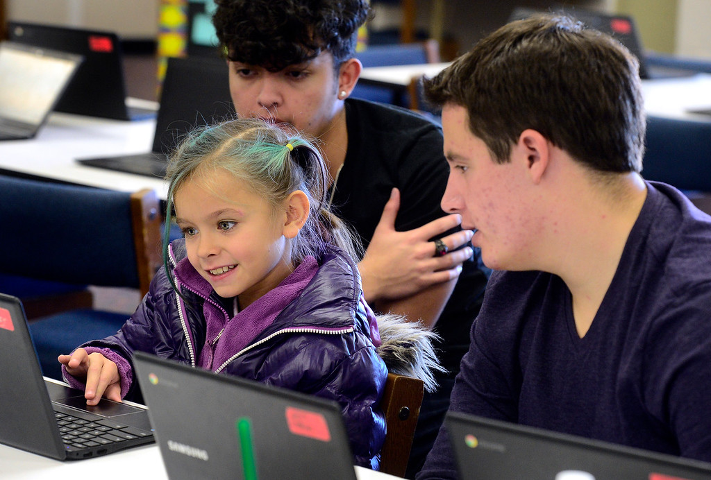 . BROOMFIELD, CO - DECEMBER 4, 2018 Makenzy Cordovan, a second grader at Centennial Elementary School, works to do coding on a program as Luke O\'Brien of Bollman Technical Education Center guides her as part of Computer Science Education Week at the school in Broomfield on Tuesday morning. For more photos go to broomfieldenterprise.com (Photo by Paul Aiken/Staff Photographer)