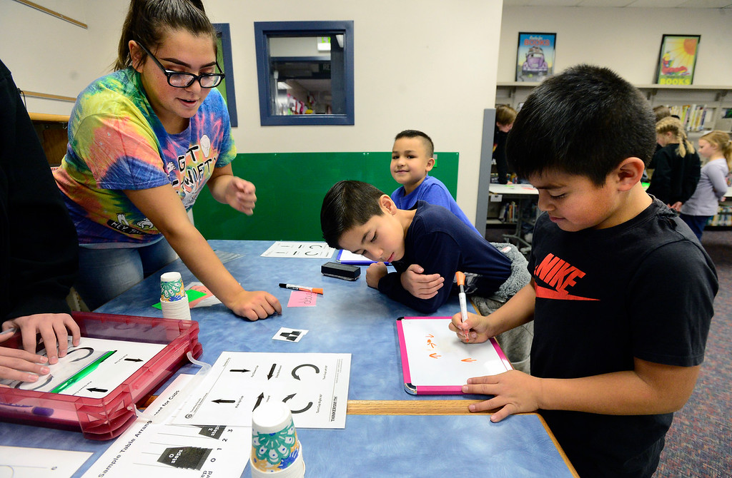 . BROOMFIELD, CO - DECEMBER 4, 2018 Centennial Elementary School second graders (front to back) Gabriel Limon, Jonathan Chavez and Alan Hermisis work to set up algorithms to represent the moves needed to stack cups as part of Computer Science Education Week at Centennial Elementary School in Broomfield. Cheyenne Calzada, of Bollman Technical Education Center, who sent students to run the students through a series of exercises, looks on at left.  For more photos go to broomfieldenterprise.com (Photo by Paul Aiken/Staff Photographer)