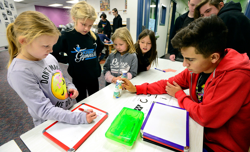 . BROOMFIELD, CO - DECEMBER 4, 2018 Centennial Elementary School students from left to right, Mckenna May, Kalissa Chapman, Bristol Amos and Vonetta Young work together to plan out work algorithms to represent the moves needed to stack cups as part of Computer Science Education Week at Centennial Elementary School in Broomfield on Tuesday morning. Alex Gutierrez, of Bollman Technical Education Center, who sent students to run the students through a series of exercises, helps the girls with the task at right. For more photos go to broomfieldenterprise.com (Photo by Paul Aiken/Staff Photographer)